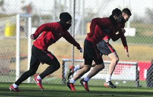 Tres jugadores del Sevilla, muy abrigados, hacen un 'sprint'...