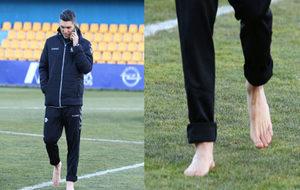 El jugador camina descalzo sobre el césped de Alcorcón.