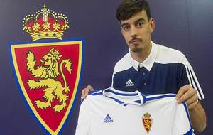 Edu Bedia posa en La Romareda con su nueva camiseta y delante del...