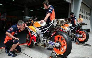 Dos mec�nicos observan la moto de M�rquez.