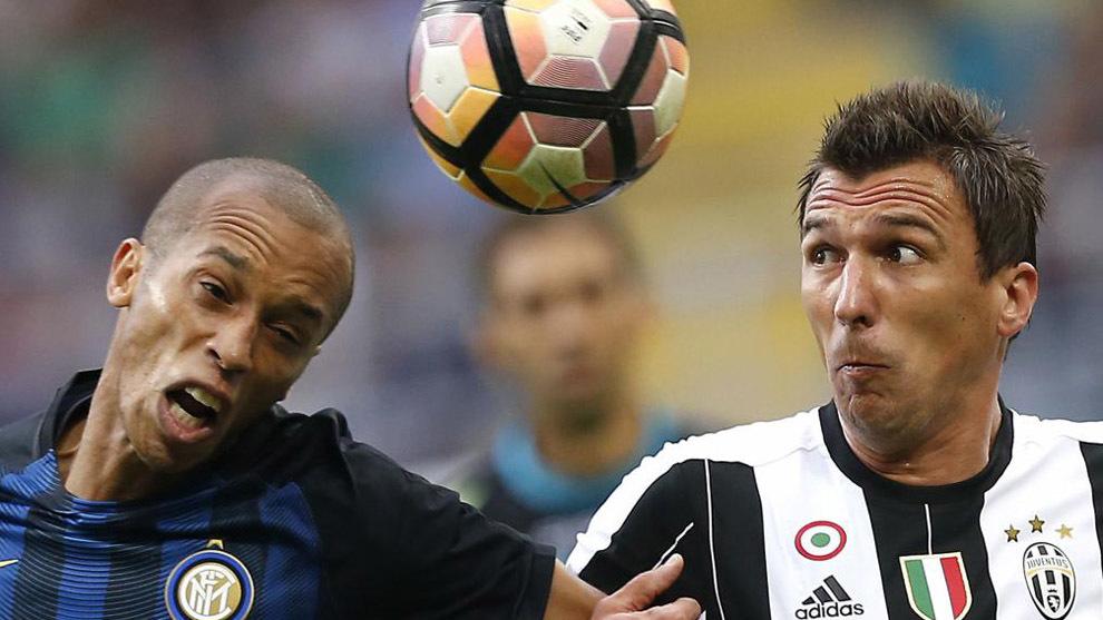 Miranda y Mandzukic pelean por un balón en una disputa Inter-Juve.