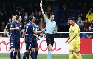 Vicandi muestra una amarilla a un jugador del Málaga.