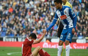 Diego Reyes ayuda a levantarse a un jugador del Sevilla.