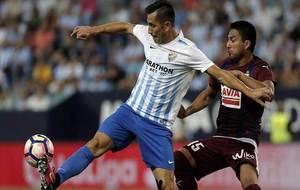 Charles, presionado por Mauro dos Santos, protege el balón.
