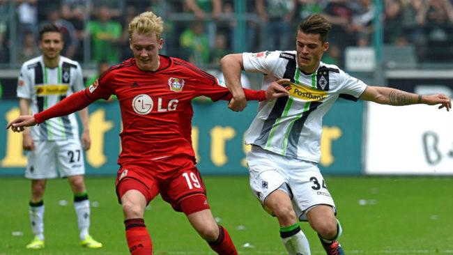 Granit Xhaka y Julian Brandt pelean por un balón en un  Borussia...