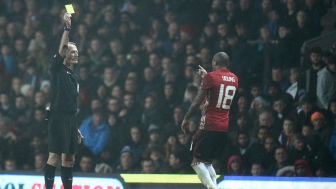 Atkinson amonesta a Young en un partido de FA Cup.