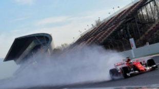 El Ferrari de Raikkonen crea una cortina de agua a su paso por la...
