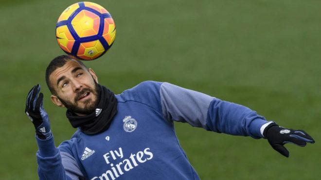 Karim Benzema controla un balón con la cabeza durante un...