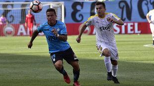 Ramos (Iquique) disputa un balón con Baéz, de blanco.