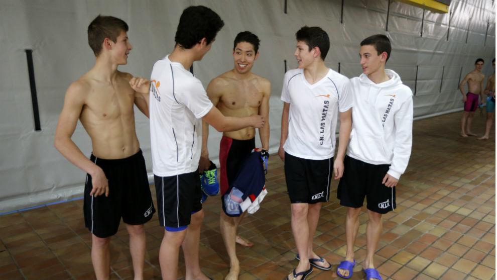 El nadador japonés atiende a un petición para fotografiarse con unos...