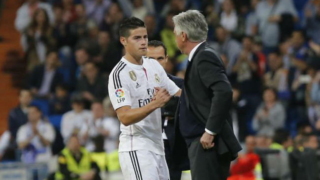 James le da la mano a Ancelotti en un partido del Real Madrid
