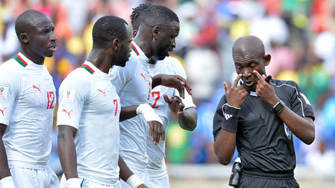 Referee Joseph Lamptey argue with Senegal players.