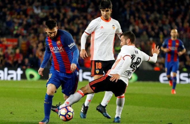 Gayá disputa un balón a Messi ante la mirada de Carlos Soler.