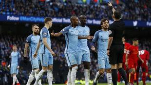 Los jugadores del City protestan a Oliver durante el duelo ante el...