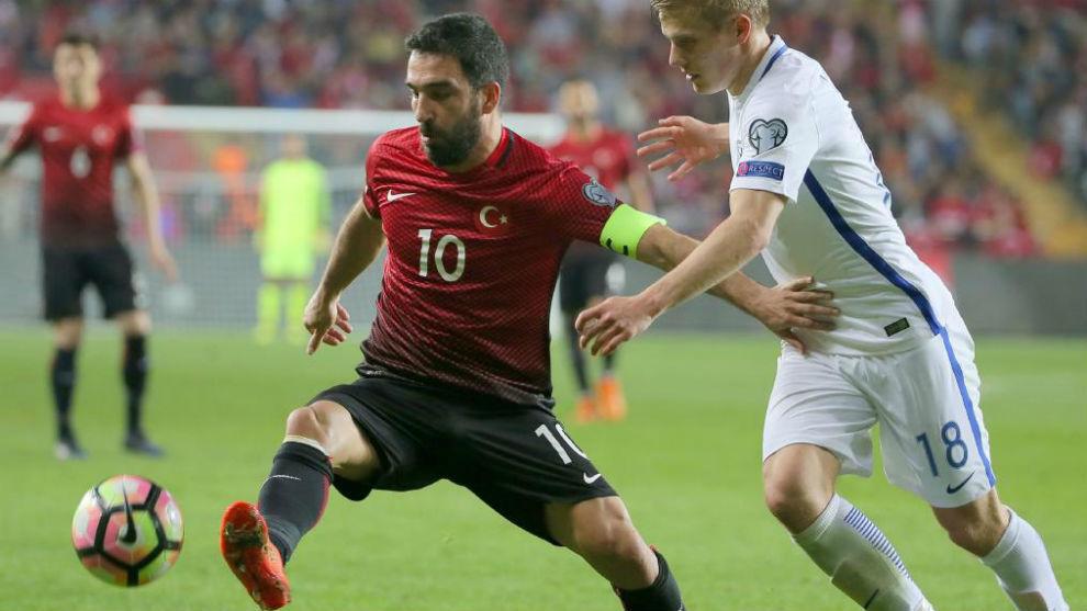 Arda Turan disputa un balón contra Fen Uronen, de la selección de...