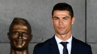 Cristiano, junto al busto que luce en el aeropuerto que lleva su...