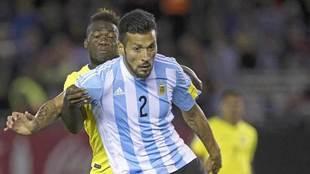 Garay, con Argentina, pugna con Caicedo en un partido.