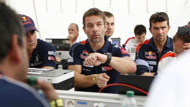 Loeb comenta algún detalle del Peugeot 3008 DKR en presencia de...