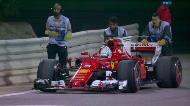Los comisarios del circuito empujan en Ferrari de Vettel hasta el...