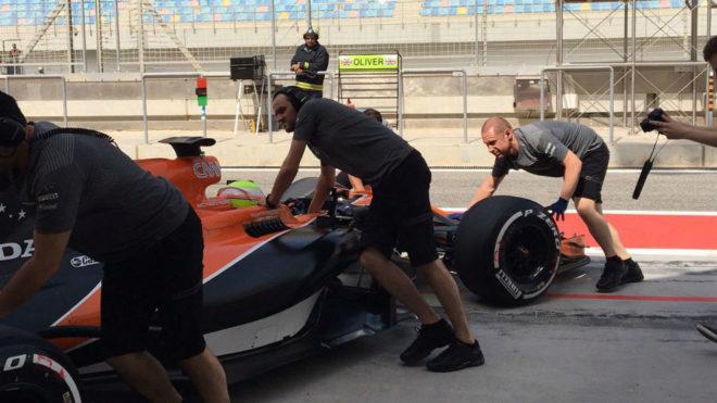 Los mecánicos de McLaren meten el coche de Oliver Turvey en el box...