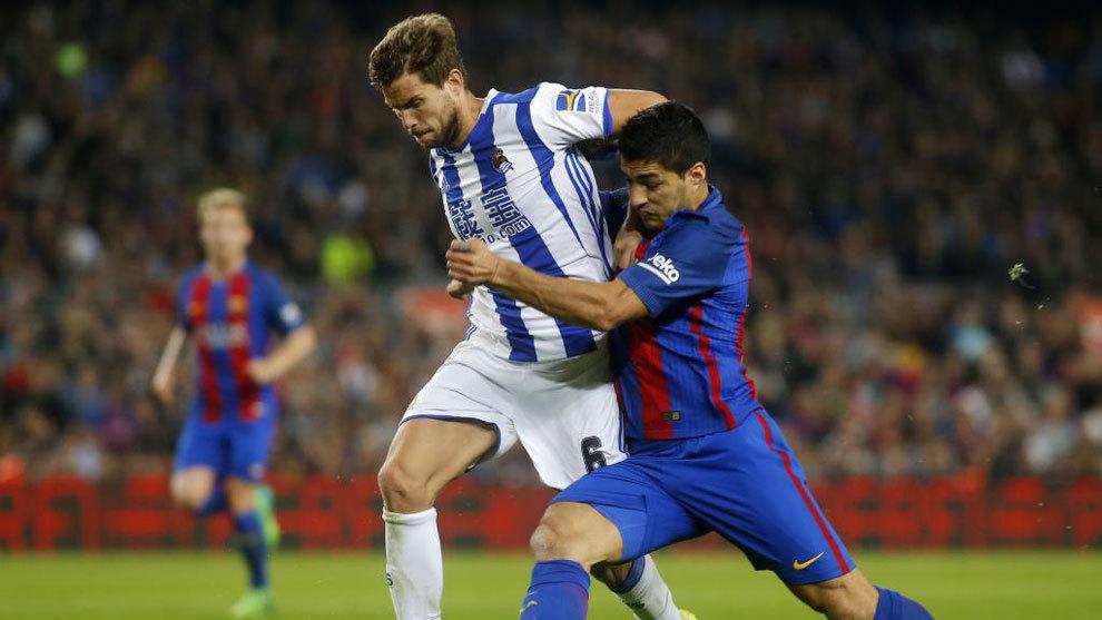 Iñigo Martínez luchando por un balón con Luis Suárez