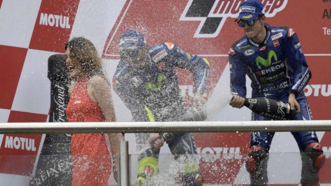 Maverick Viñales y Valentino Rossi bañan en champán a una azafata...