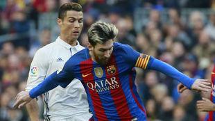 Cristiano Ronaldo y Leo Messi luchan por un balón