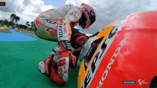 Márquez intenta levantar su moto tras caer en el GP de Francia.