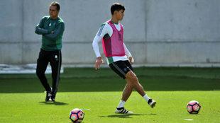 Mando golpea un balón en un entrenamiento, con Alexis a su espalda.