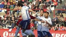 Raúl Cámara despeja de cabeza, delante de Carlos Ruiz y Alberto, en...