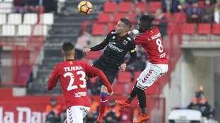 Madinda disputa un balón aéreo con Julio Álvarez en presencia de...