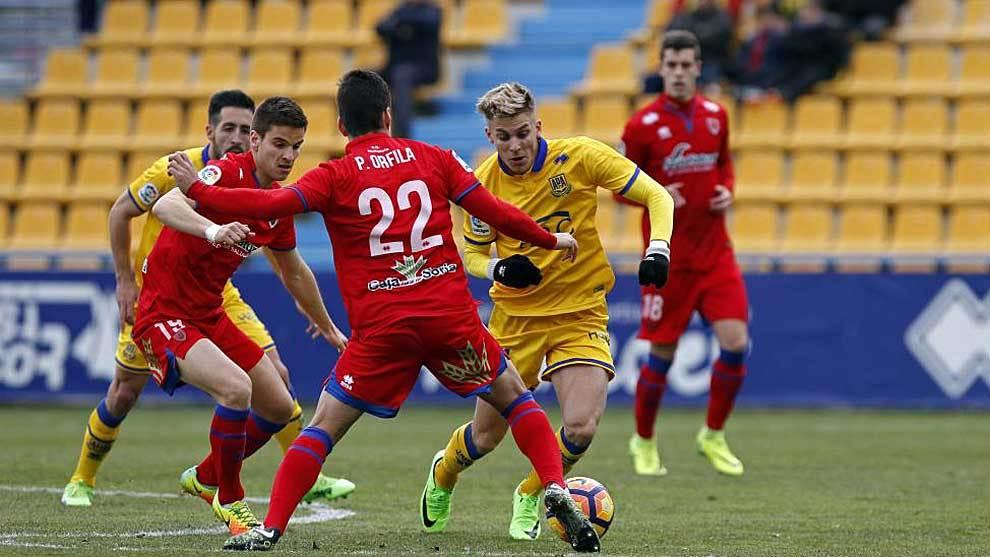 Iván Alejo, rodeado por jugadores del Numancia en el partido de Santo...