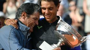 Toni Nadal entrega el trofeo de Roland Garros a su sobrino Rafa.