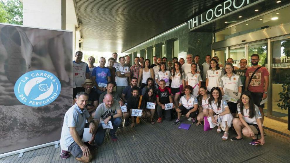 Los participantes en La Carrera del Peregrino posan ante la puerta del...