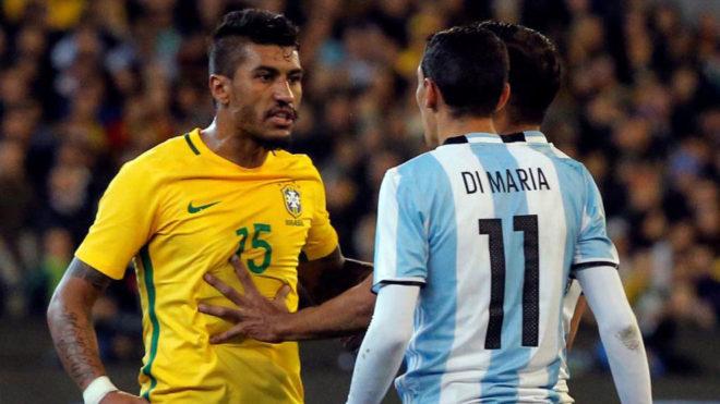 Paulinho se encara con Di María en un partido entre Brasil y...