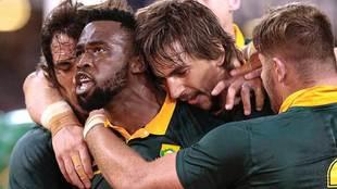 Siya Kolisi es abrazado por Eben Etzebeth y otros compañeros tras su...