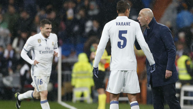 Varane recibe instrucciones de Zidane con Kovacic al fondo.