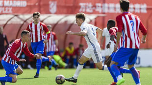 Llario conduciendo el balón ante la oposición de varios juveniles...