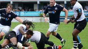 Ross Road es placado por dos jugadores fijianos durante el encuentro...