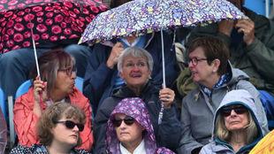 La gente, en la grada con paraguas