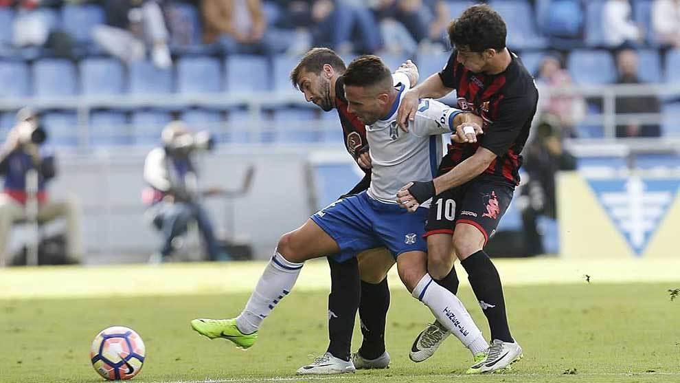 Aarón Ñíguez es frenado por dos jugadores del Reus en el partido...
