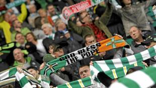 Un aficionado del Celtic porta una bandera con los colores irlandeses...
