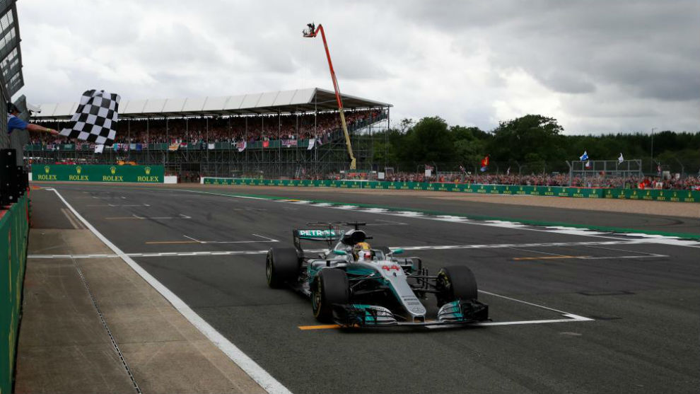 Mercedes' British driver Lewis Hamilton crosses the finish line to...