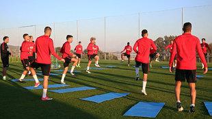 Los jugadores del Atlético de Madrid se entrenan sobre el césped en...