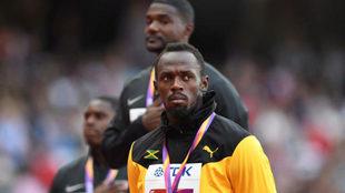 Usain Bolt, con su bronce mundial, en primer plano. Gatlin justo...