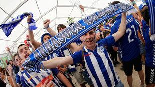 Aficionados del Alavés posan con una bufanda del club
