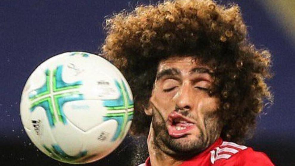 Fellaini (29) recibe es golepeado por un balón durante el partido por...
