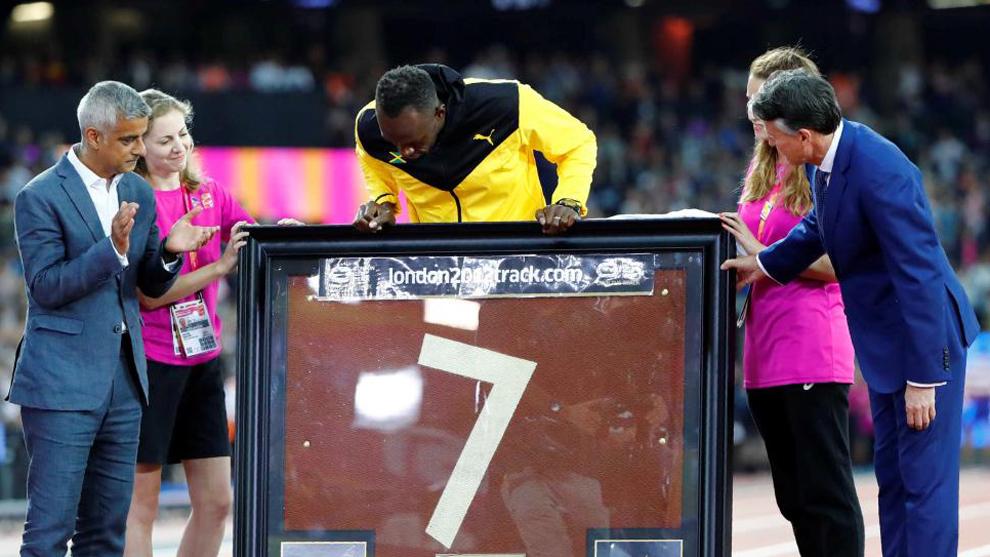 Usain Bolt (30) recibe una pieza de una pista de tartán como homenaje...