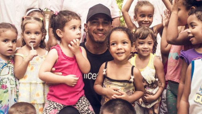 Hamilton, rodeado de niños durante su visita a Cuba.