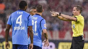 El árbitro Tobias Stieler hace un gesto en referencia al VAR durante...